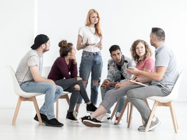 Sad red-haired girl talking about depression during group meeting with therapist